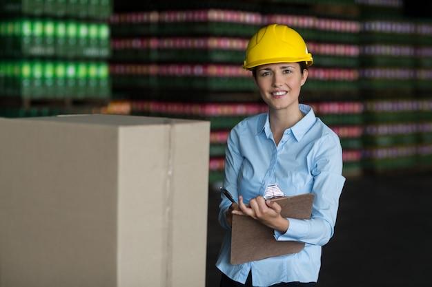 Żeński pracownik fabryczny utrzymuje rejestr na schowku w fabryce