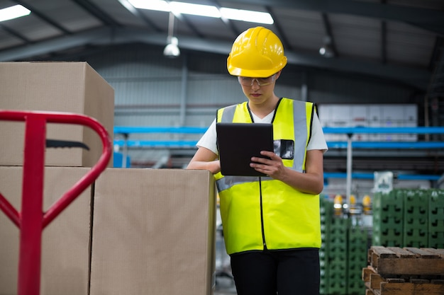 Żeński pracownik fabryczny używa cyfrową pastylkę w fabryce