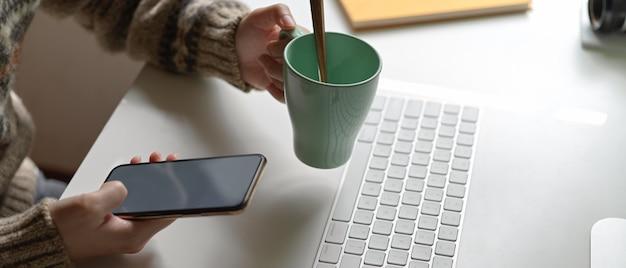 Żeński pracownik relaksuje z smartphone i trzyma filiżankę kawy przy biurowym biurkiem