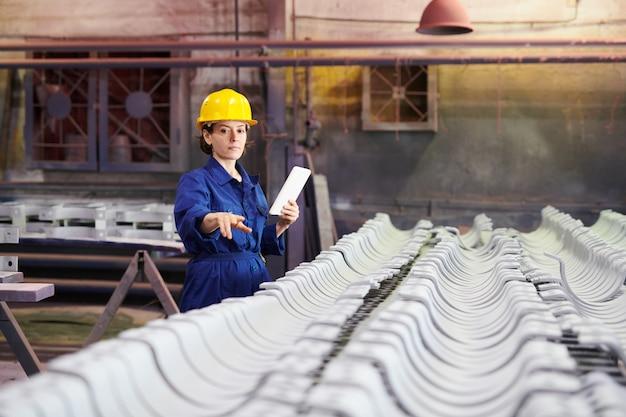 Żeński pracownik sprawdza produkcję