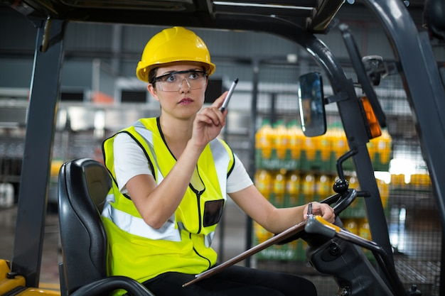 Żeński pracownika fabrycznego obsiadanie na wózku widłowym i writing w schowku przy fabryką