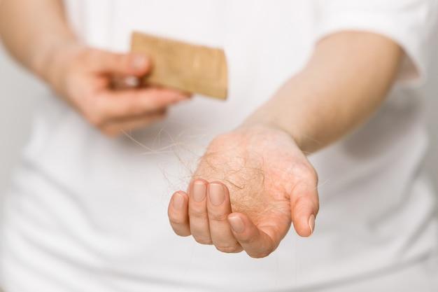 Żeński przegrywający włosy po czesania w hairbrush w ręce, selekcyjna ostrość