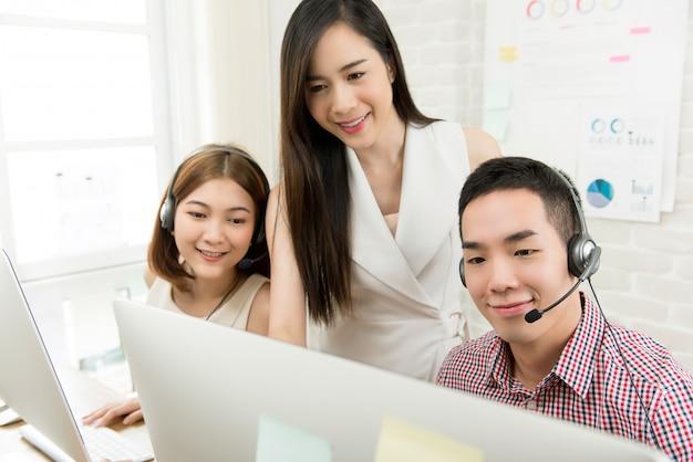 Żeński przełożony dyskutuje pracę z zespołem agenta obsługi klienta telemarketingu w call center