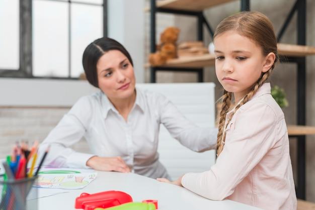 Żeński psycholog pocieszający przygnębionej dziewczyny w biurze