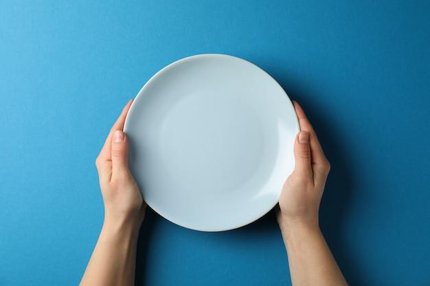 Żeński ręka chwyta talerz na błękitnym tle, odgórny widok
