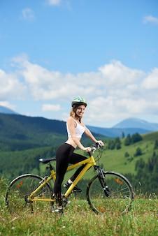 Żeński rowerzysta na żółtym rowerze