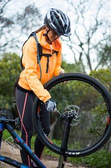 Żeński rowerzysta naprawia rower górskiego