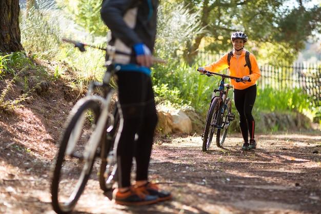 Żeński rowerzysty odprowadzenie z rowerem górskim na drodze polnej