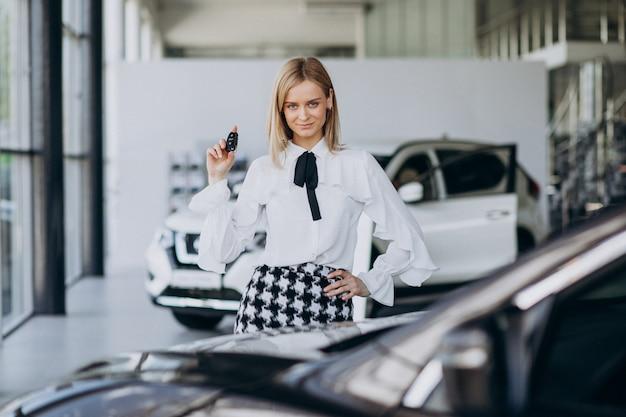 Żeński sprzedawca przy samochodową sala wystawową pozycją samochodem