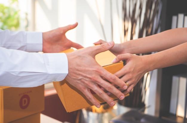 Żeński sprzedawcy domu biznesowy właściciel obchodzi się pakunek klient