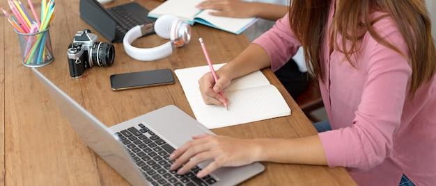 Żeński student uniwersytetu bierze notatkę na pustym notatniku podczas gdy szukający w formaci na laptopie w bibliotece