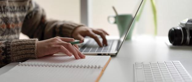 Żeński student uniwersytetu przygotowywa informacje dla jej prezentaci z laptopem i pustym notatnikiem