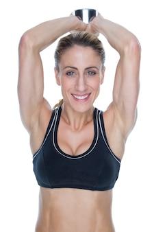 Żeński szczęśliwy bodybuilder pracujący z wielkim dumbbell za głową out