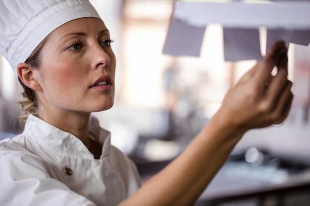 Żeński szef kuchni patrzeje listę rozkazów w kuchni