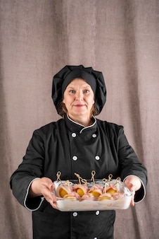 Żeński szef kuchni trzyma bekonowego naczynie