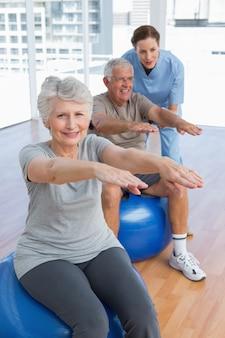 Żeński terapeuta pomaga starszej pary z ćwiczeniami