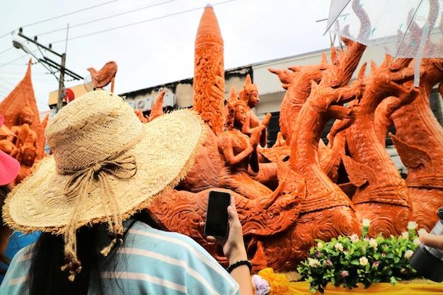 Żeński turystyczny bierze fotografię wielka świeczka z telefonem komórkowym w ubon ratchathani świeczki festiwalu, tajlandia.