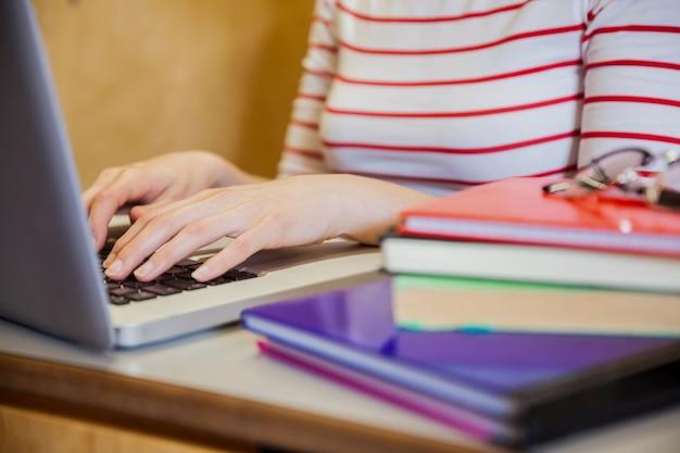 Żeński uczeń pisać na maszynie na laptopie przy uniwersytetem