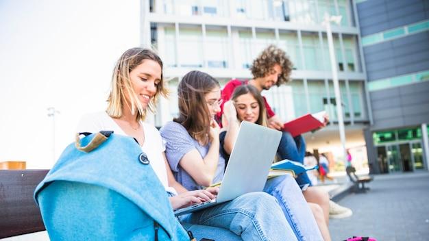 Żeński używa laptop blisko studiować przyjaciół