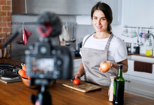 Żeński vlogger nagrywa kucharstwo odnosić sie transmisję w domu