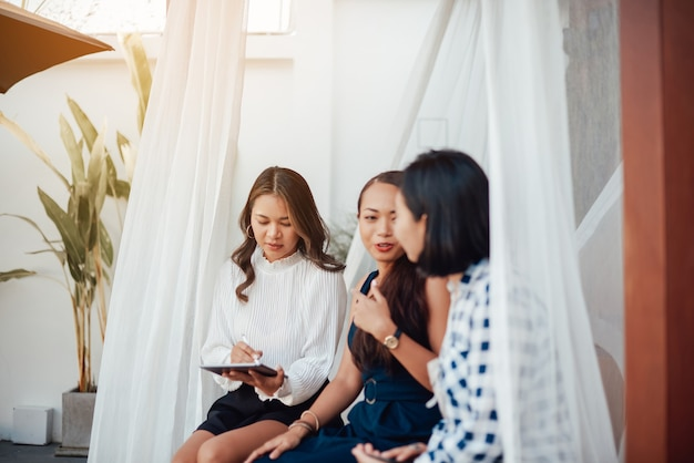 Żeński zespół azjatyckich kobiet pracuje siedząc na progu rezydencji i omawia swoje plany w ciągu dnia.
