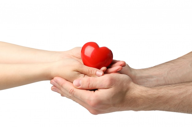 Żeńskie i męskie ręki trzymają serce, odosobnionego na biel przestrzeni