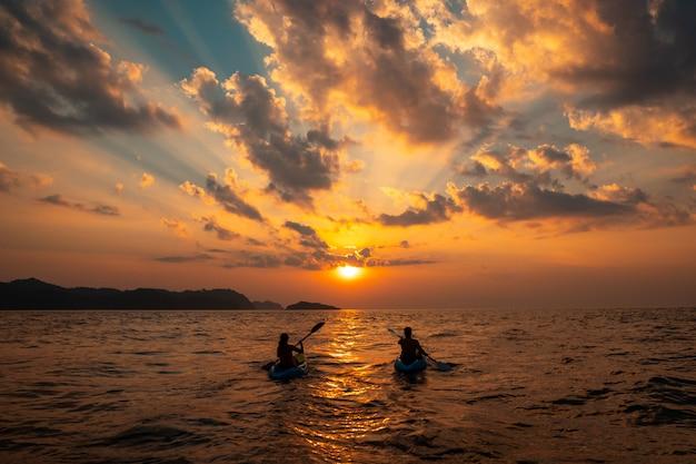 Żeńskie i męskie żeglowanie z kajakami blisko siebie o zachodzie słońca