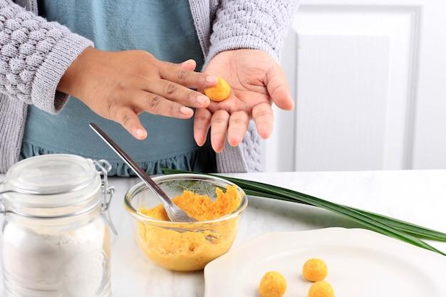 Żeńskie indonezyjskie ręcznie zaokrąglanie biji salak kabocha, żółte słodkie ziemniaki lub ciasto ryżowe z dyni, proces gotowania w kuchni przygotowanie takjil na śniadanie w buka puasa ramadan