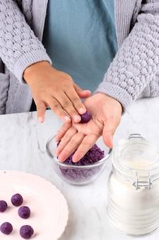 Żeńskie indonezyjskie ręcznie zaokrąglanie biji salak ubi ungu, purpurowe słodkie ziemniaczane ciasto ryżowe, proces gotowania w kuchni przygotowanie takjil na śniadanie buka puasa ramadan