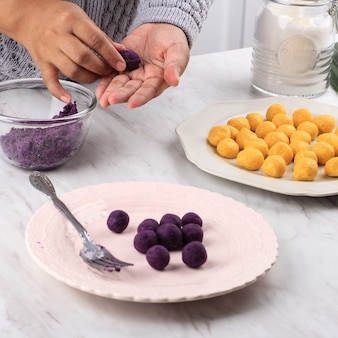 Żeńskie Indonezyjskie Ręcznie Zaokrąglanie Biji Salak Ubi Ungu, Purpurowe Słodkie Ziemniaczane Ciasto Ryżowe, Proces Gotowania W Kuchni Przygotowanie Takjil Na śniadanie Buka Puasa Ramadan Premium Zdjęcia