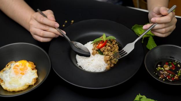 Żeńskie jedzenie wymieszaj smażoną mieloną wieprzowinę z bazylią (pad ka prao), smażone jajka i sos rybny chili w tajskiej restauracji