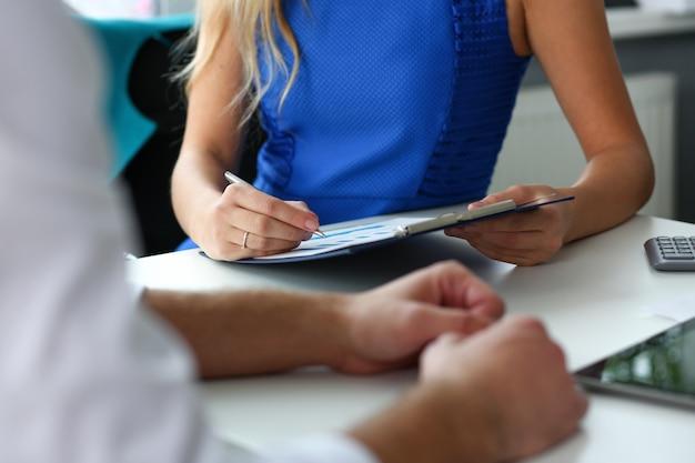 Żeńskie ramię trzymać srebrny długopis bada statystyki grafiki