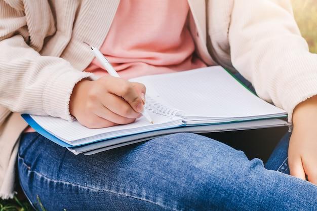 Żeńskie ręki piszą w notatniku.