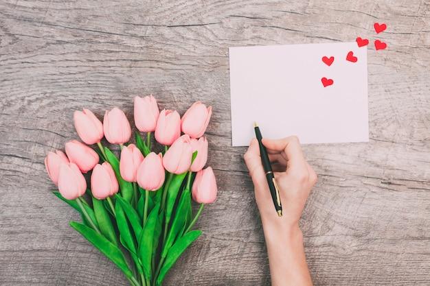 Żeńskie ręki piszą wiadomości miłość na białej kopercie na drewnianym tle. walentynki