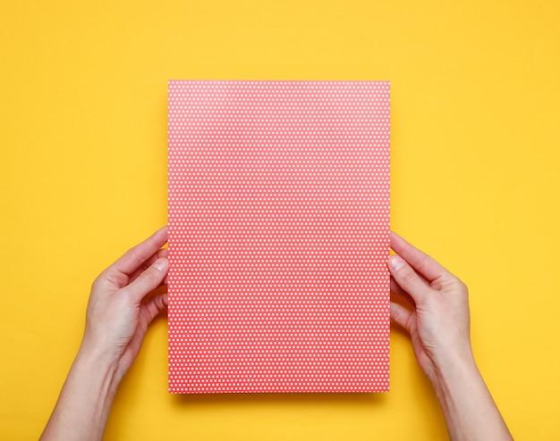 Żeńskie ręki trzyma papierowego prześcieradło z polki kropką na kolorze żółtym