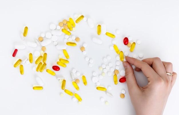 Żeńskie ręki trzymają coloured pigułki na białym tle. widok z góry. koncepcja zdrowia.