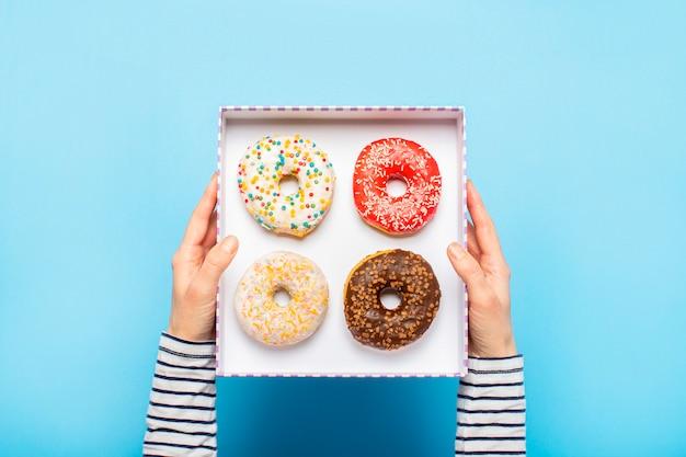 Żeńskie ręki trzymają pudełko z pączkami na błękicie. koncepcja cukierni, cukierni, kawiarni.