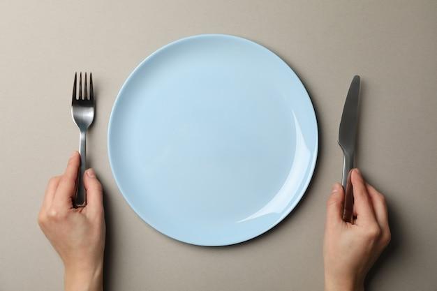 Żeńskie ręki trzymają rozwidlenie i nóż na szarość wykonują ręcznie tło z talerzem, odgórny widok