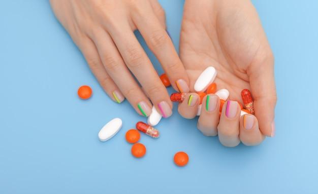 Żeńskie ręki z pięknym nowożytnym manicure'em i pigułkami