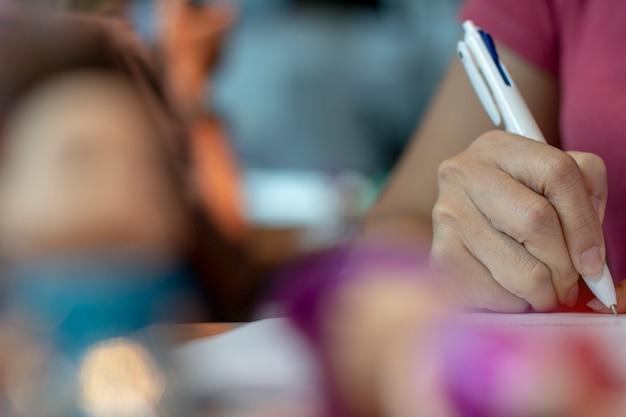 Żeńskie ręki z pióra writing na notatniku