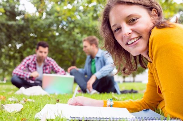 Żeńskie writing notatki z uczniami używa laptop w parku