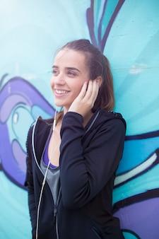 Żeńskiego jogger słuchająca muzyka na telefonie komórkowym przed graffiti ścianą