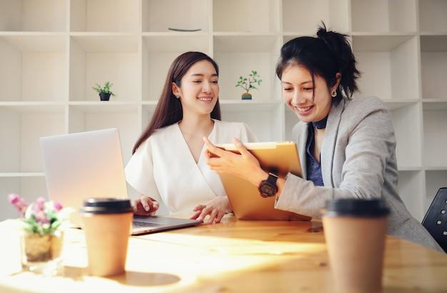 Żeńskiego pracownika chwyta pastylka i opowiadający biznes z partnerem pijemy kawę podczas gdy praca od domu