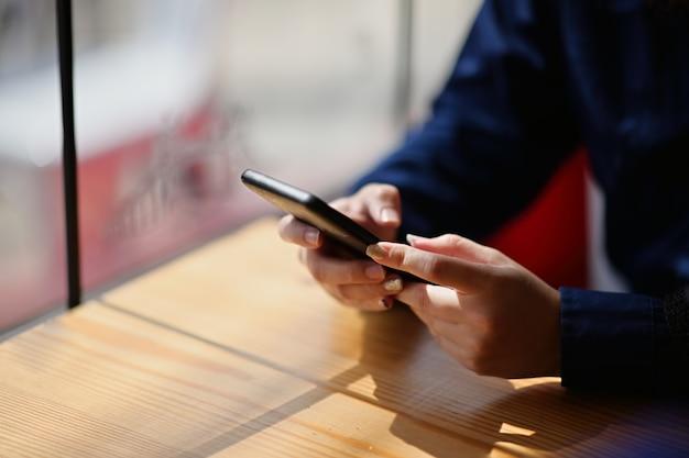 Żeńskiego ręki mienia mobilny mądrze telefon w kawiarni
