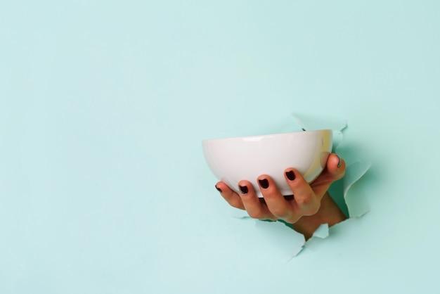Żeńskiej ręki mienia pusty puchar na błękitnym tle z kopii przestrzenią.