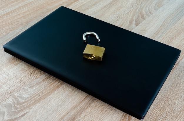 Zepsuta kłódka na zamkniętym laptopie, koncepcja naruszenia bezpieczeństwa internetu i technologii lub kradzieży danych