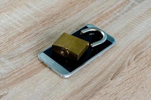 Zepsuta kłódka na zepsutym smartfonie, koncepcja naruszenia bezpieczeństwa internetu i technologii lub kradzieży danych