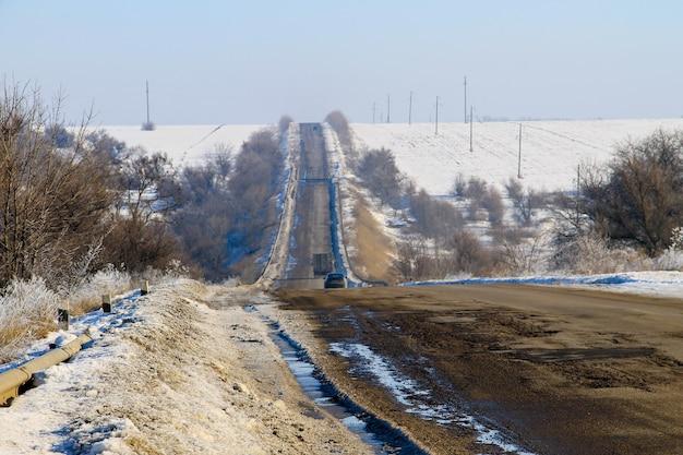 Zepsuta popękana asfaltowa droga zimą