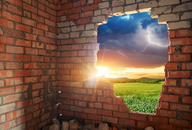 Zepsuta ściana z cegieł i krajobraz