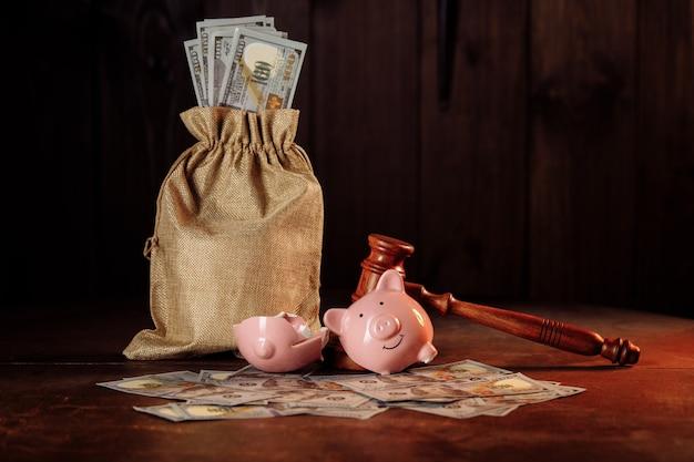 Zepsuta skarbonka z torbą na pieniądze i koncepcją inwestycji i bankructwa sędziego młotkiem